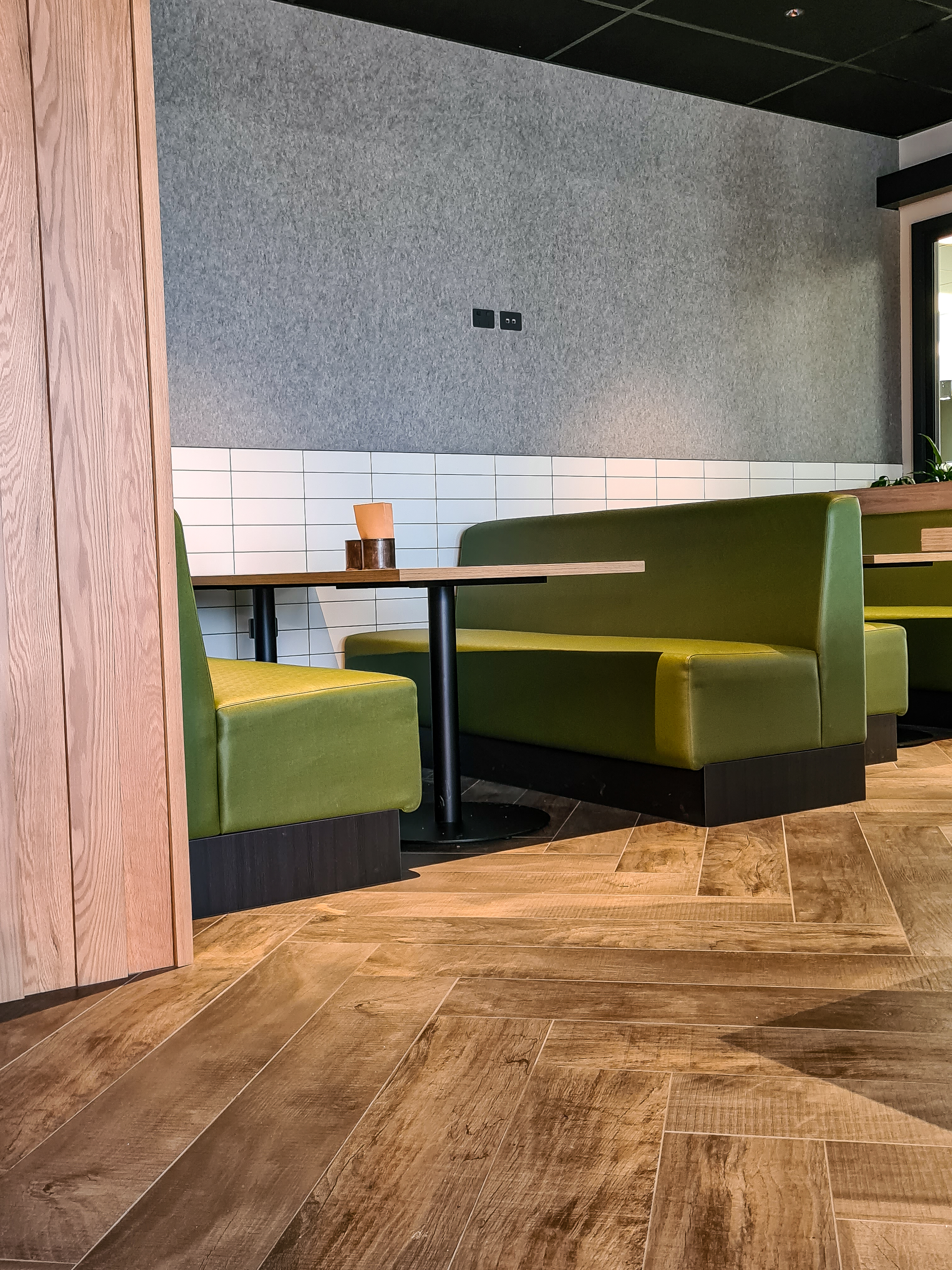 Lunchroom: Woodlands Grey Tiles with White wall matt 100x300 tiles on the wall. This space also featured the acoufelt solid panels metal on the wall.